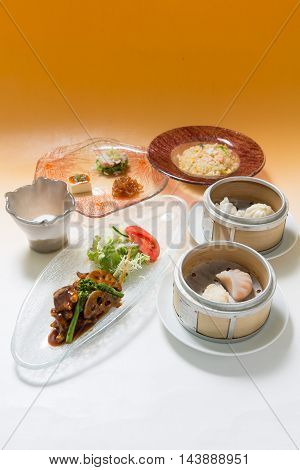 Courses of japanese meal with dumplings, sauteed meat and rice on white background