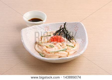 Japanese noodle of Hakata Mentai Mayo Udon with soyal sauce on wooden table