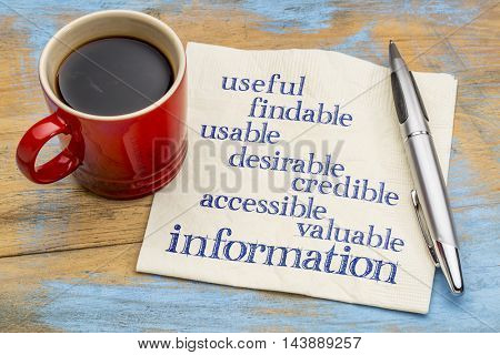 user experience concept - attributes of information important for usability and user experience on a napkin with a cup of coffee
