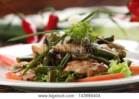 Special plate of mix salad with green bean lettuce herbs and fried pork in restaurant