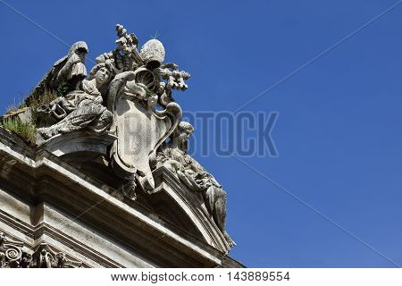 Pope emblem between angels at the top of Ss Luca and Martina baroque church in Rome designed by Pietro da Cortona in the 17th century (with copy space)