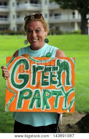 August 6, 2016: Idaho USA a woman holds a sign and asks for donations and signatures in support for the Green Party movement for president. Aug. 6, 2016