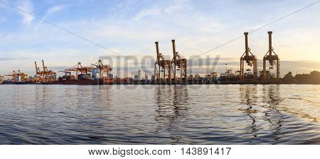 Panorama view working crane loading bridge in shipyard at sunrise time for Logistic Import Export background