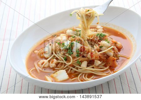 Pasta noodle with seafood scallop and squids in white bowl on wooden table