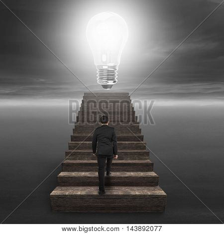 Glowing Bulb On Wooden Stairs With Businessman Climbing