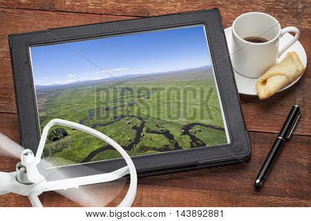 aerial photography concept - reviewing aerial pictures of the Illinois River (North Park, Colorado) on  a digital tablet with a drone rotor and coffee, screen picture copyright by the photographer