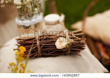 decorations for a photo shoot in the style of shabby chic branches and brushwood tied with string with flower lying on a beige linen fabric