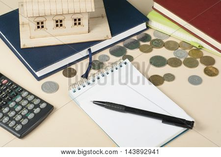 Home savings, budget concept. Model house, notepade, pen, calculator and coins on wooden office desk table