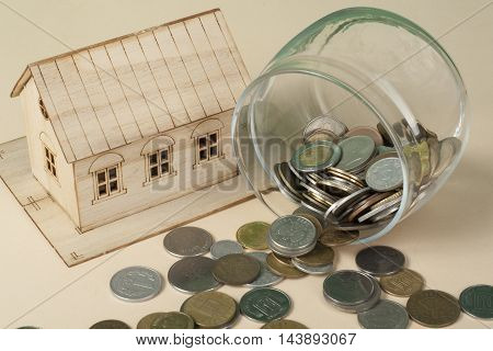 Saving to buy a house, real estate or home savings. Piggy bank, coins and toy model.