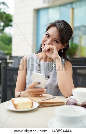 Laughing pretty woman sitting at cafe tablet