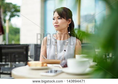 Pensiv attractive woman sitting at coffee tablet