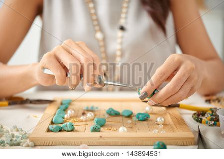Jewelry designer using pliers in her work