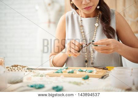 Cropped image of woman concentrated on creation of new jewelry piece