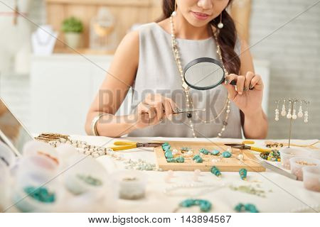 Jewelry designer looking at her work with magnifying glass