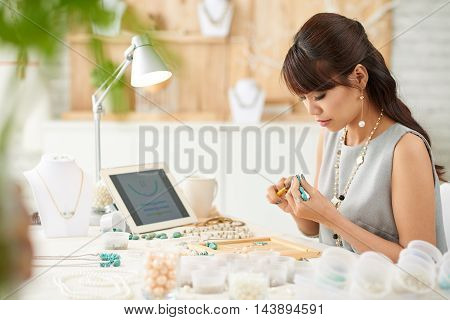 Pretty Vietnamese woman working with gemstones in her studio