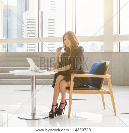 Thai business women, smart women sitting on co working space with notebook in the office