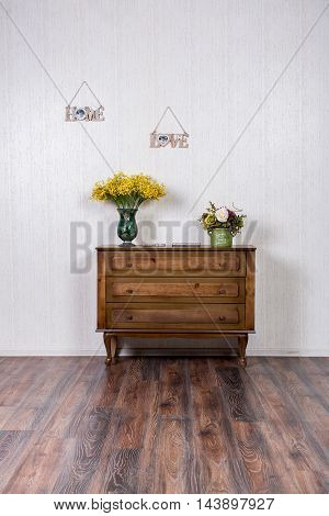 Dresser in home inrerrior decorated with flovers and plates