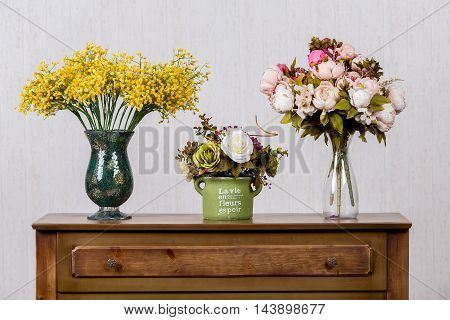 Three vases with colorful flovers on dresser in home inrerrior