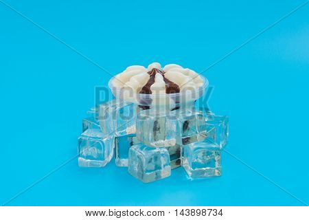 side view cup of chocolate flavor ice cream and ice cube on blue background