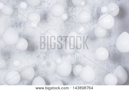 White party balloons infronrt of gray texture wall