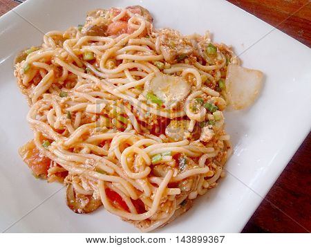 Spaghetti on white dish with wooden table