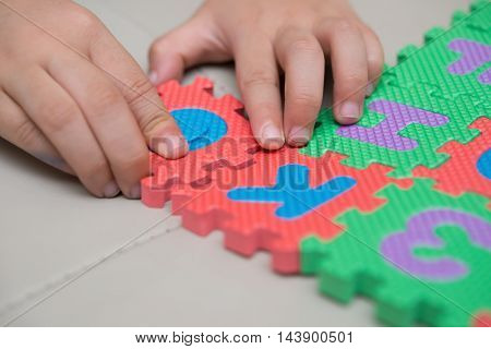 kid playing alphabet jigsaw puzzles  horizontal composition