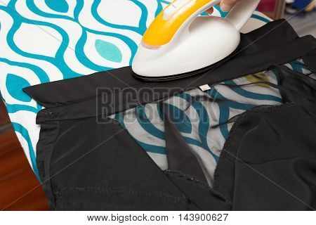 woman ironing clothes on ironing board  horizontal composition