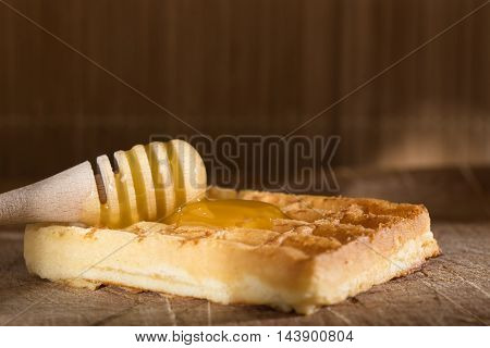 Honey on a fresh waffles over wooden background