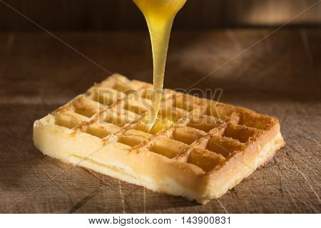 Honey pouring on a fresh waffles over wooden background