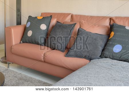 Modern Living Room Design With Brown Leather Sofa And Black Pillows