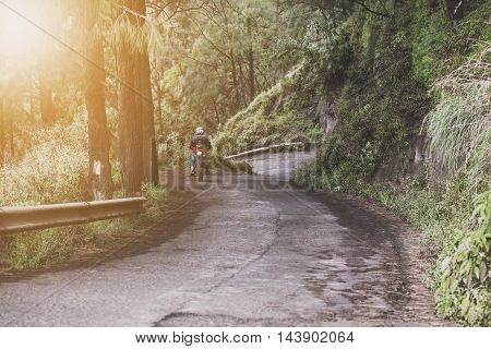 Motorcycle riding downhill on concrete road, with bright sunlight, vintage tone
