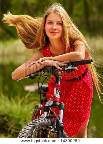 Bicycle girl. Girl wearing sundress rides bicycle into park. Girl in ecotourism. Bicycle is good for health. Bicycle girl have long blond hair.Long hair of bicycle girl fluttering in wind.