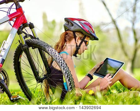 Girl wearing bicycle helmet sitting near bicycle and watch pc tablet. Bicycle girl looking with interest pc tablet.
