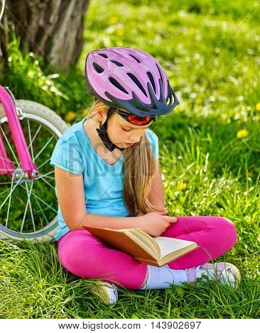 Girl rides bicycle. Girl in bicycle helmet read book on rest near bicycle. Cycling is good for health. Cyclist looking at camera. Camping Reading.
