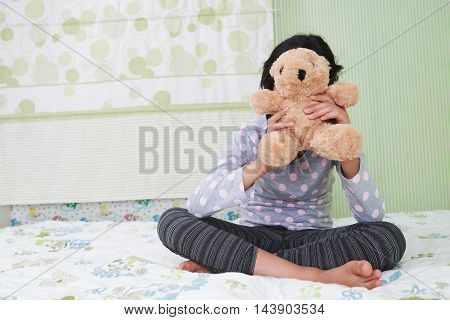 Girl sitting on bed and hiding behind her teddy bear