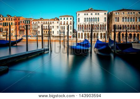 Venice cityscape view on Grand canal with colorful buildings and boats at the sunrise. Long exposure image technic with motion blurred boats and glossy water
