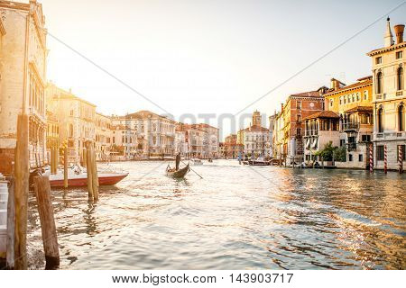 Venice cityscape view on Grand canal with colorful buildings and gondola floating on the sunset