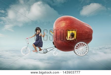 Happy sister enjoy with fantasy apple cycle ride .