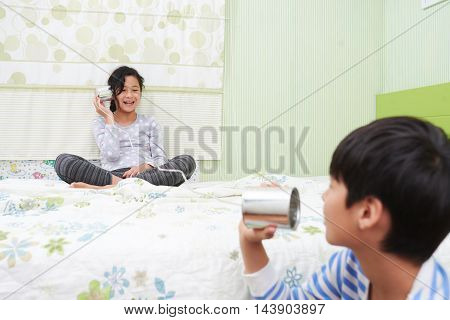 Mixed-race children enjoying playing together with tin phone