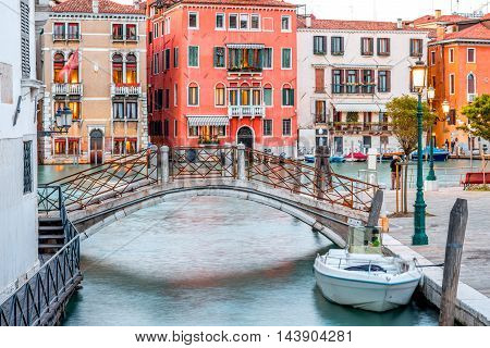 Small romantic water canal with bridge at the dusk in Venice