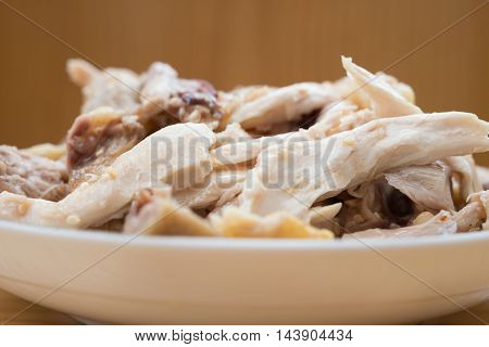 dish of shredded boiled chicken on wood table close up