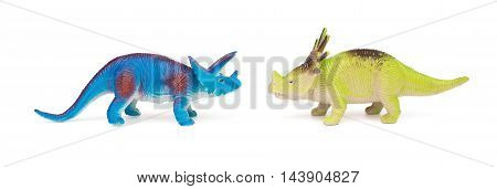blue triceratops and green styracosaurus toys on a white background