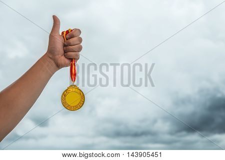 man lifting a gold medal with the thumb up