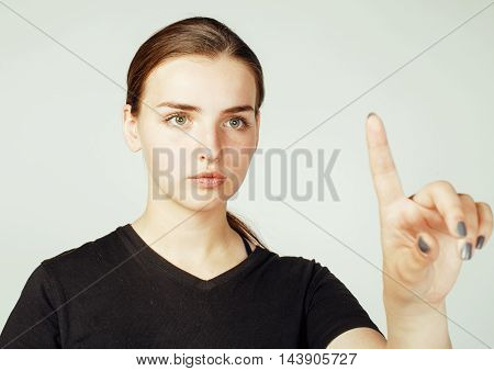 young pretty brunette girl pointing on white background, business science people concept