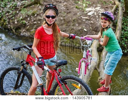 Two girl rides bicycle. Two girl cycling fording throught water . Cycling trip is good for health. Cyclist watch your step. Eldest bicycle girl helping bicycle younger girl.