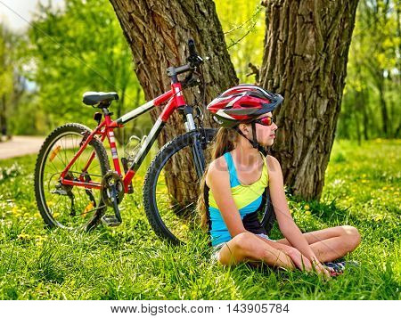 Bikes cycling girl. Girl rides bicycle. Girl in cycling sitting near bicycle. Cycling is good for health and mood. Cyclist dreamily looking into distance. Beautiful nature around.