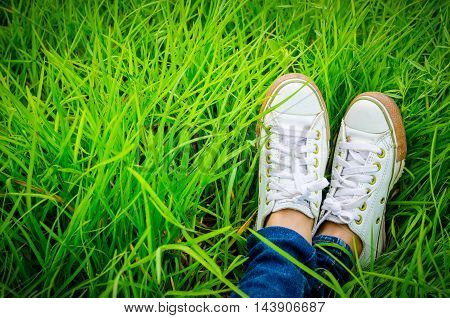 Shoes of a teenager woman who is sitting on grass field