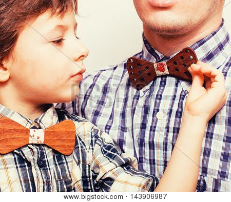 father with son in bowties on white background, casual look close up