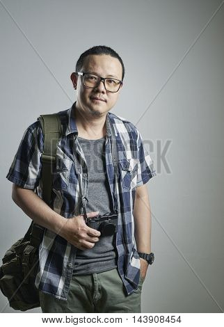 Travel concept. Studio portrait of young man hold a camera.