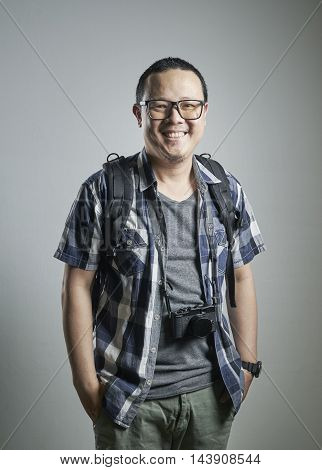 Travel concept. Studio portrait of young man with a camera.